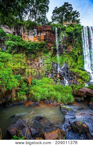 Thin stream of one of the many waterfalls. The concept of extreme and ecological tourism. Argentina, Iguazu Falls