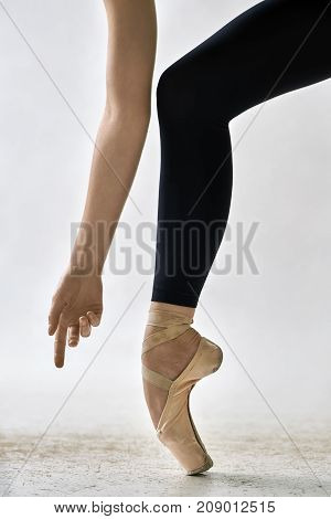 Beautiful ballerina is posing in the studio on the light background. She stands on the toe and holds the arm next to the leg. Girl wears black leggings and beige pointe shoes. Closeup. Vertical.