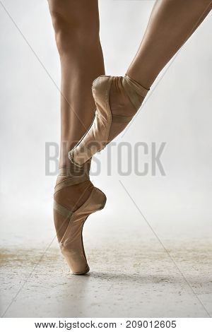 Elegant ballerina is posing in the studio on the light background. She stands on the right toe and holds left leg in the air. Girl wears beige pointe shoes. Closeup. Vertical.
