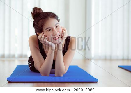 Young Happy Woman Relaxing On Yoga Mat In Gym
