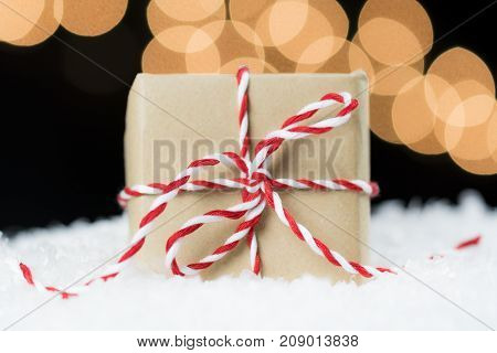 Vintage Paper Wrapped Gift With Red And White Twine On Snow