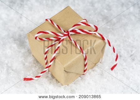 Hand Wrapped Plain Paper Small Gift Box Tied With Red And White Twine, Sitting On Snow