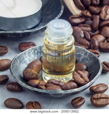 Coffee essential oil in a glass bottle on background with coffee beans square format