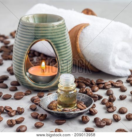 Aroma lamp with coffee essential oil on woven mat spa background square format