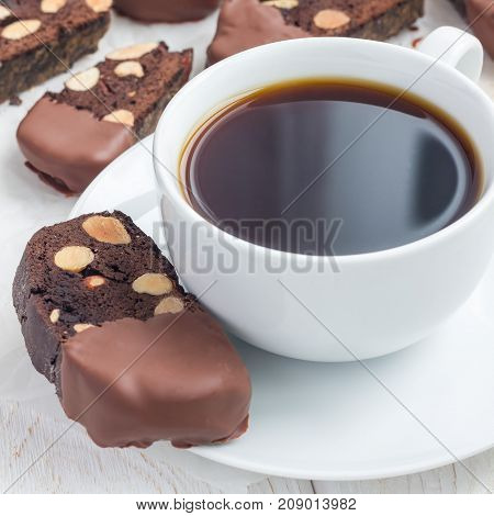 Homemade dark chocolate biscotti cookies with almonds covered with melted chocolate and a cup of coffee square format