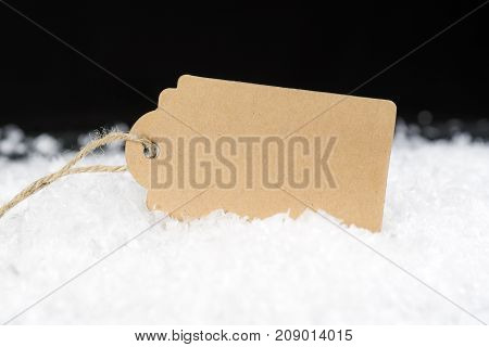 Simple Decorative Cardboard Gift Tag Or Sale Label Sitting In Snow Against Black Background