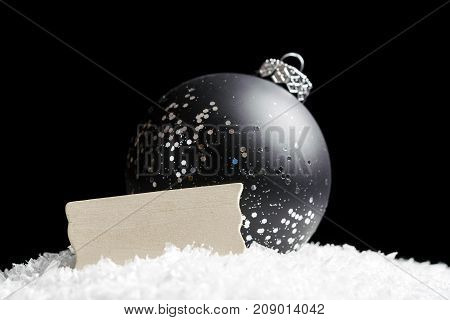 Blank Wooden Sign And Black And Silver Glittering Ornament Sitting In Snow