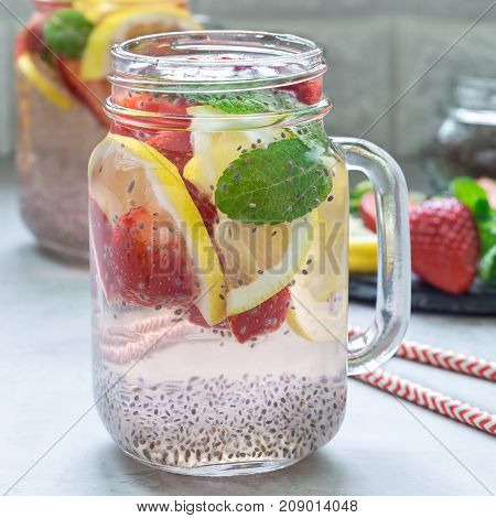 Healthy detox chia seed drink with strawberry lemon and mint in a glass jar square format
