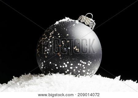 Glittering Black And Silver Ornament Sitting In Snow, Shining In Light On Black Background