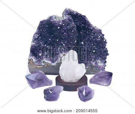 Clear quartz cluster surrounded by amethyst purple druse geode and amethyst points,   isolated on white background