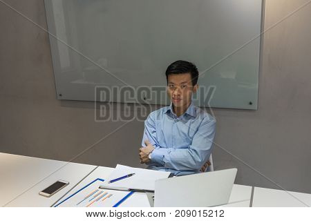 Confident, handsome Asian businessman sitting in his meeting room
