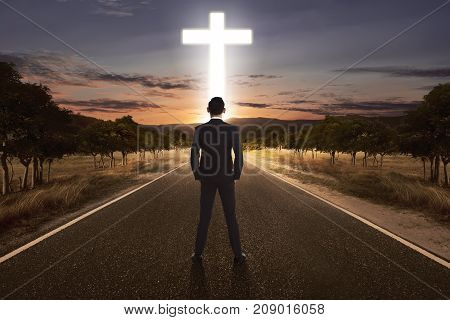 Back View Of Man Standing On The Street With Bright Cross