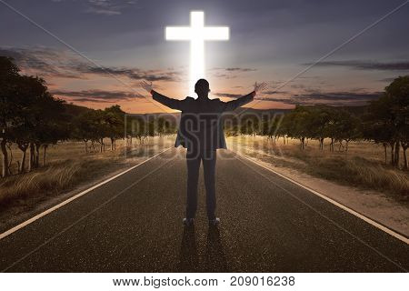 Portrait Of Man Raising Hand While Praying To God With Bright Cross