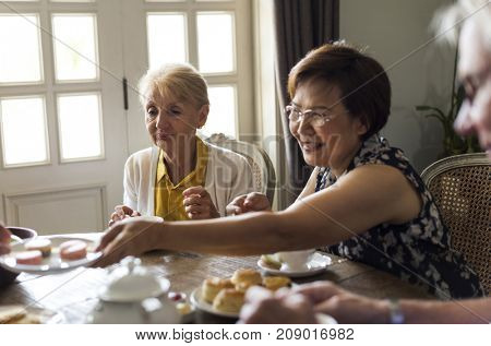 Elderly people having tea party together