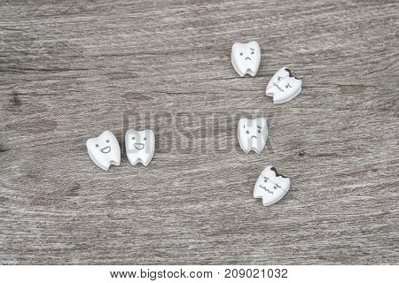 human oral health icon - cute healthy and crying decayed teeth on wood