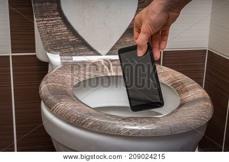 Woman Throwing Mobile Phone In The Toilet Bowl
