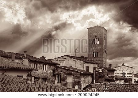 Tower of Chiesa San Pietro with roofs of historic buildings and sun ray in background in Lucca, Italy.
