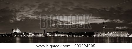 Venice skyline at night with Santa Maria della Salute church and clock tower historical architectures panorama in Italy.