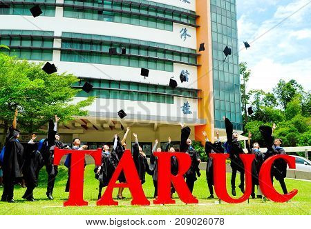 Setapak Kuala Lumpur Malaysia. August 27 2017:Beautiful young graduates with diplomas toss their mortar boards into the air in front of Tunku Abdul Rahman Universiti College (TARUC).TARUC is a leading public university in Malaysia.