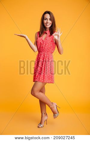 Full length image of smiling brunette in dress holding copyspace on the pound and showing ok sign while looking at the camera over yellow background