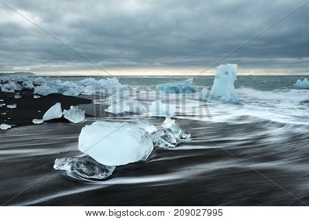 Icy beach in Iceland, Europe. Ice on the black volcanic sand on the Atlantic Ocean. Tourist attraction. Amazing landscape. World beauty
