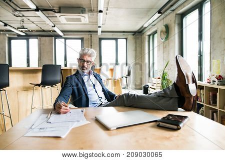 Thoughtful mature businessman with gray hair in the office sitting with legs on desk, working.