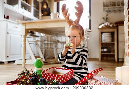 Cute little girl at Christmas time blowing party whistles. Daughter wearing reindeer headband.
