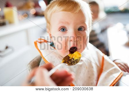 Cute baby boy sitting in highchair eating. Two small children in a kitchen.