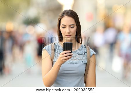 Serious Girl Checking Phone Message On The Street