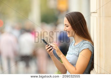 Side View Of A Girl Checking A Smart Phone On The Street