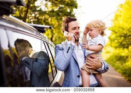Young father holding his little boy in the arms going into the car. Man with smartphone making a phone call.
