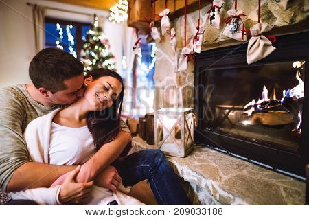 Beautiful young couple sitting on the floor in front of fireplace, relaxing. Man kissing woman on her neck. Christmas time.