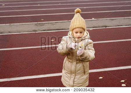 Little 4 year-old girl in a beige woolen hat and warm holding a little yellow flower on a race track.