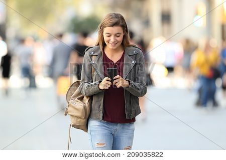 Fashion Girl Walking Texting On A Phone On The Street