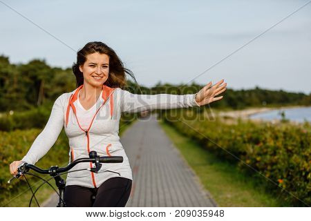 Young woman riding bike at seaside