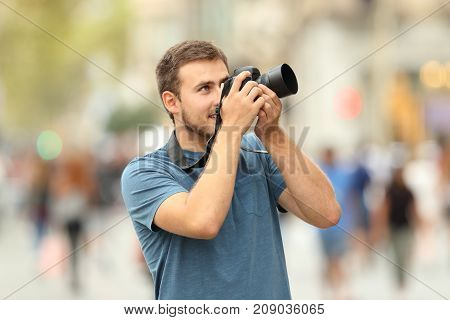Happy photographer taking photos on the street with a dslr camera
