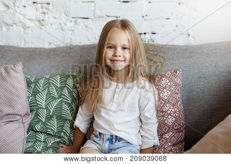 Adorable 5-year old blue eyed little girl of European appearance sitting on comfortable couch with decorative pillows dressed in jeans shorts and white blouse enjoying free time after kindergarten