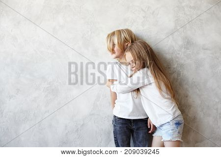 Sweet romantic little couple enjoying nice time together. Adorable girl hugging tight tall boy with blonde hair. Cute sister embracing her brother after long separation. Love romance and childhood