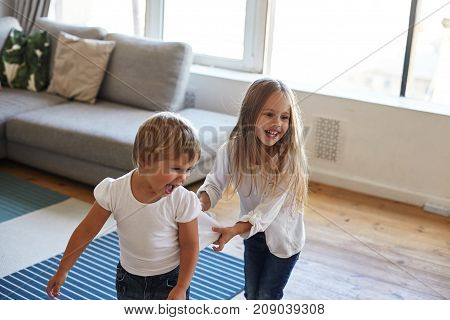 Candid shot of happy cheerful female child with long straight hair having excited look pulling her little sister by t-shirt while standing in conga line playing funny game together being home alone