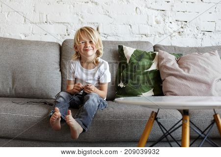 Portrait of mischievous naughty boy with long blonde hair sitting on grey couch at home wearing jeans and white t-shirt looking at camera with sly mysterious smile while planning joke or trick