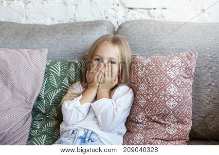 Pretty little girl with long straight hair sitting on grey sofa covering face with both hands her eyes expressing fear shame or shock. Human facial expressions emotions feelings and body language
