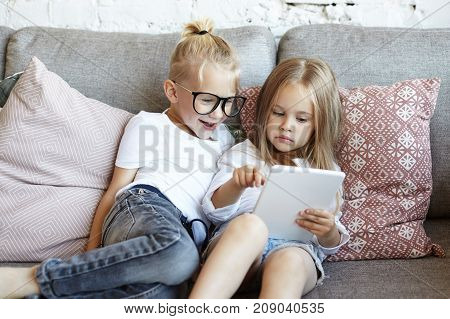 Adorable little female child holding electronic device sitting on grey sofa with elder brother in glasses showing him how to play video game online. Children communication leisure and technology