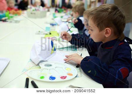 Child coloring a baseball cap at table