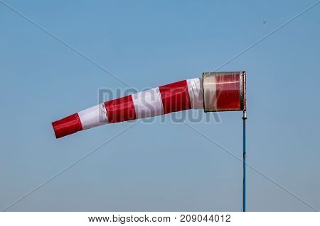 Airport windsock on clear blue sky background in windy weather indicate the local wind directionair sock drogue wind sleeve wind cone poster
