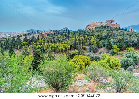 Parthenon and Herodium construction in Acropolis Hill in Athens, Greece. Beautiful landscape with green trees around ancient architecture.