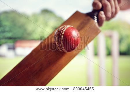Cricket batsman hitting a ball shot from below with stumps on cricket pitch
