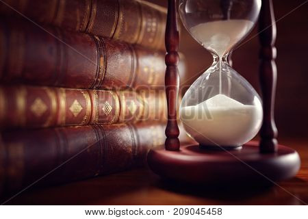 Old books and hourglass in library