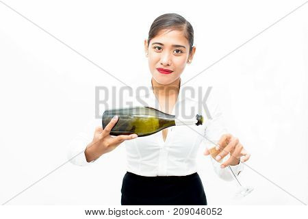Portrait of confident young Asian waitress or businesswoman pouring champagne in flute and looking at camera. Drinks and office party concept