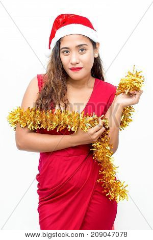 Portrait of confident young Asian woman wearing red dress and Santa hat, posing with tinsel in hands. Christmas and New Year concept