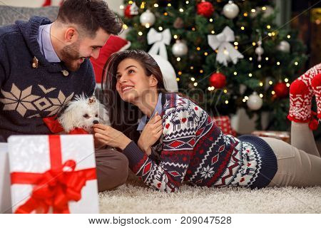 smiling boyfriend giving puppy dog as Christmas present to girlfriend